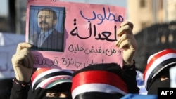 "A Yemeni woman holds a sign bearing a doctored picture of President Ali Abdullah Saleh behind bars with text that reads, ""Wanted for justice... The one who captures him will be rewarded,"" during a pro-democracy demonstration in Sanaa in late October."
