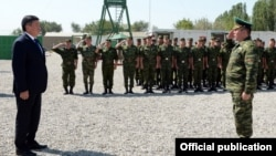 Kyrgyz President Sooronbai Jeenbekov (left) with members of the country's border guards (file photo)