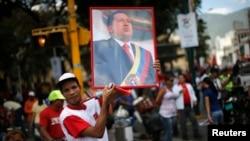 Сторонник президента Венесуэлы Уго Чавеса держит плакат с его изображением во время митинга в Каракасе, 27 февраля 2013 года.