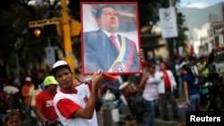 Участник акции в поддержку президента Венесуэлы Уго Чавеса с его портретом в руках. Каракас, 27 февраля 2013 года.