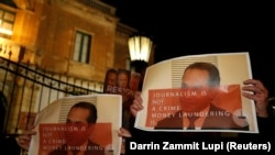 Protestors hold up posters showing Pilatus Bank chairman Ali Sadr Hashemi Nejad while calling for the resignation of Malta's police commissioner, outside police headquarters in Floriana, March 21, 2018