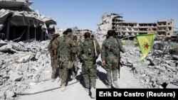 Syrian Democratic Forces troops walk past the ruins of destroyed buildings near the National Hospital in Raqqa on October 17.