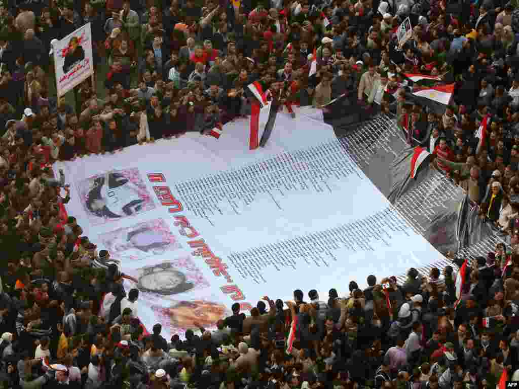 Antigovernment protesters carry a huge banner with the names and pictures of victims killed during the protests.