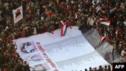 محتجون في ميدان التحرير يحيطون لافتة بصور وأسماء ضحايا الإحتجاجات