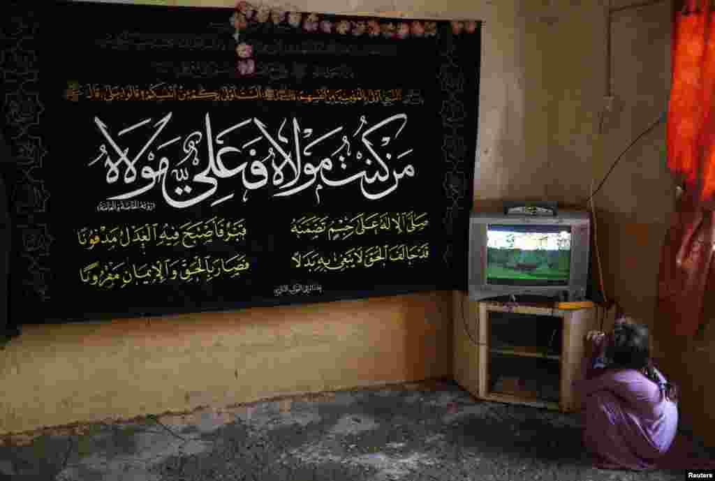 A girl watches television at home in the Al-Fdhiliya district.