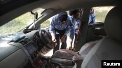 Police collect evidence from the car in which Chaudhry Zulfikar was traveling when he was attacked.