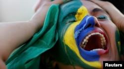 Бразилиялық жанкүйер құрамасының жеңілгеніне қайғырып отыр. Бразилия, 8 шілде 2014 жыл.