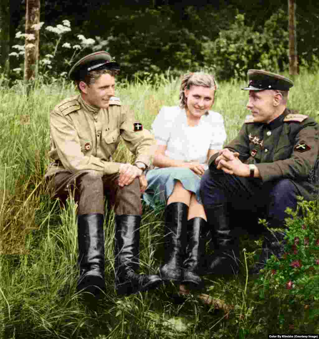 Soldiers from an Soviet antitank artillery unit sit with a woman during World War II.