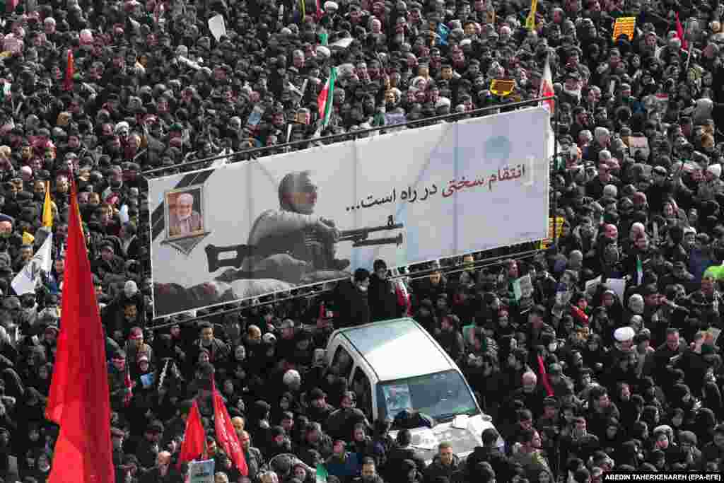 "Iranian mourners carry a huge banner showing the image of Qasem Soleimani with the slogan ""hard revenge is on the way."""