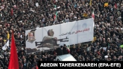 "Iranian mourners carry a huge banner with poster of Qassem Soleimani and slogans reading in Persian ""hard revenge is on the way"". January 6, 2020"