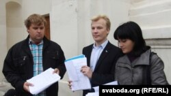 Мікалай Дзямідзенка, Віталь Рымашэўскі і Наста Палажанка паказваюць стосы лістоў з подпісамі.