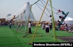 Дети и взрослые катаются на качелях. Астана, 5 июля 2012 года.