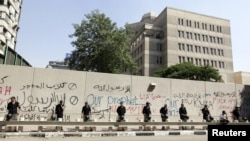 Egyptian security personnel stand guard near a wall with graffiti at the U.S. Embassy in Cairo, where protesters gathered to condemn a film being produced in the United States that insulted the Prophet Mohammad.