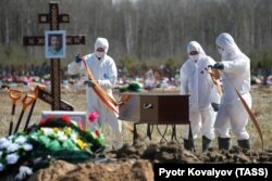 Gravediggers wearing personal protective equipment carry a coffin while burying a COVID-19 victim near St. Petersburg on May 6.