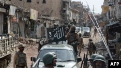 Pakistani soldiers patrol a destroyed bazaar in North Waziristan. (file photo)