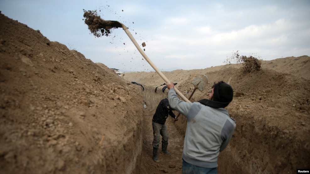 Syrian rebel fighters dig a trench on the fourth day of the truce near the rebel-held besieged city of Douma, in the eastern Damascus suburb of Ghouta, on January 2.