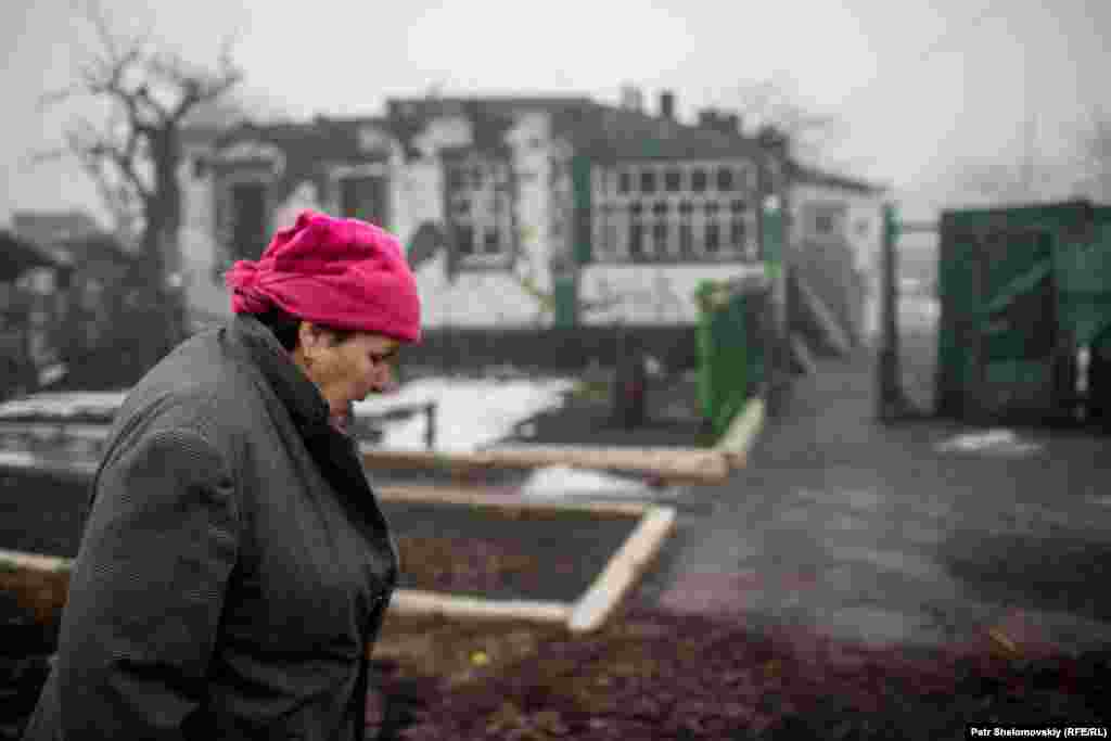 Polina Ivanovna Demianenko, 78, in front of her destroyed house in the village of Nikishine