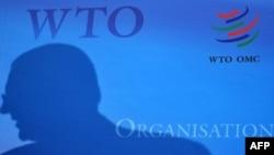 Силуэт человека на баннере с официальным логотипом ВТО. Иллюстративное фото.