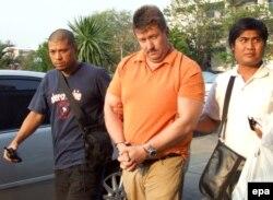 Эми эле камакка алынган Виктор Бутту Тай полициясынын гражданча кийинген офицерлери түрмөгө алып баратышат. 6-март 2008