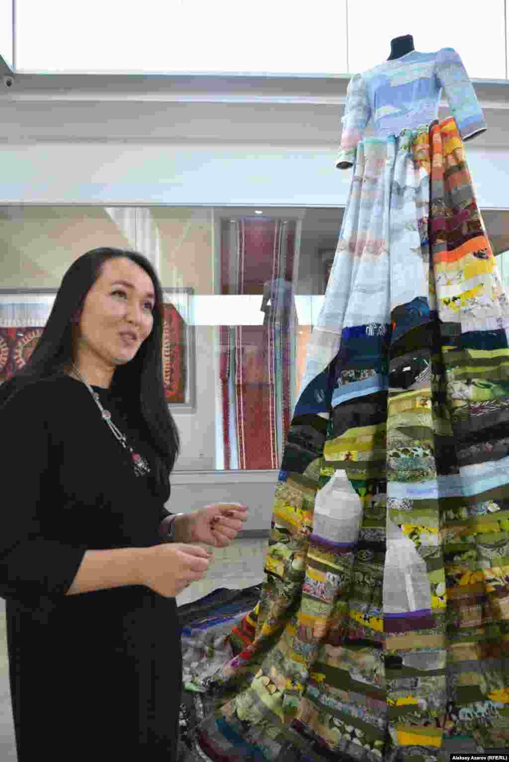 Гаухар Ахметова для коллекции создала два платья – «Дружба народов» и «Томирис». На этом фото она около «Дружбы народов». Это платье передает многонациональность Казахстана (более 120 народов). Это выражено через использование разных тканей, создающих единую картину. По словам Гаухар, когда она делала платье, то представляла себя художником, рисующим кусочками ткани.