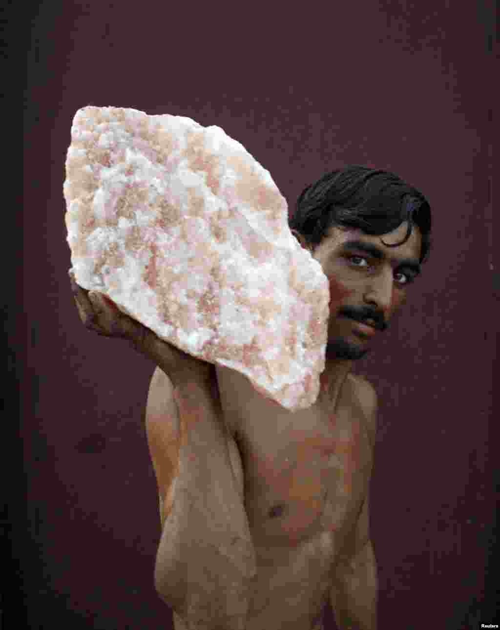 A laborer, carrying rock salt for loading onto a railway carriage, stops to pose for a photo on a train-station platform in Khewra.