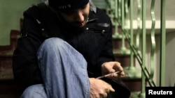 Russia -- A drug user injects heroin on a staircase in an apartment block in Moscow, November 14, 2010