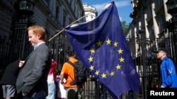 Мужчина с флагом Евросоюза за пределами Даунинг-стрит в Лондоне после объявления итогов референдума. 24 июня 2016 года.