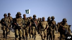 Pakistani troops walk on a hilltop post near Ladha, a town in the tribal region of South Waziristan in May 2011