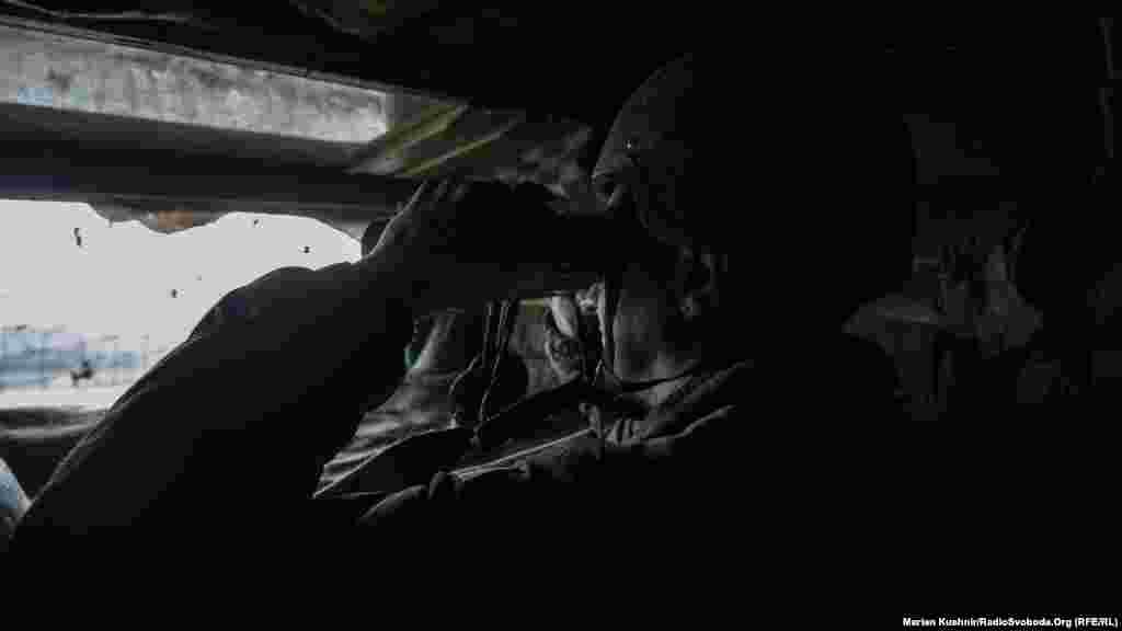 Український солдат спостерігає, що відбувається по той бік лінії фронту