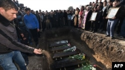 Armenia -- A man throws a handful of soil on coffins of victims during a funeral ceremony held for the six members of the same family allegedly killed by Russian soldier Valery Permyakov in the city of Gyumri, at the city's local cemetery, January 15, 2015