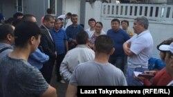 Посол Кыргызстана в России Болот Отунбаев (справа) говорит с родственниками погибших в здании типографии во время пожара. Москва, 27 августа 2016 года.