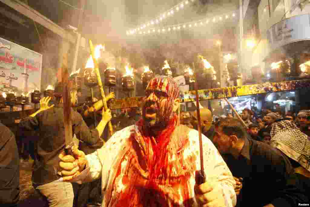An Iraqi Shi'ite Muslim man gashes his forehead with a sword before the religious festival of Ashura in Najaf on November 11. (Reuters/Alaa Al-Marjani)