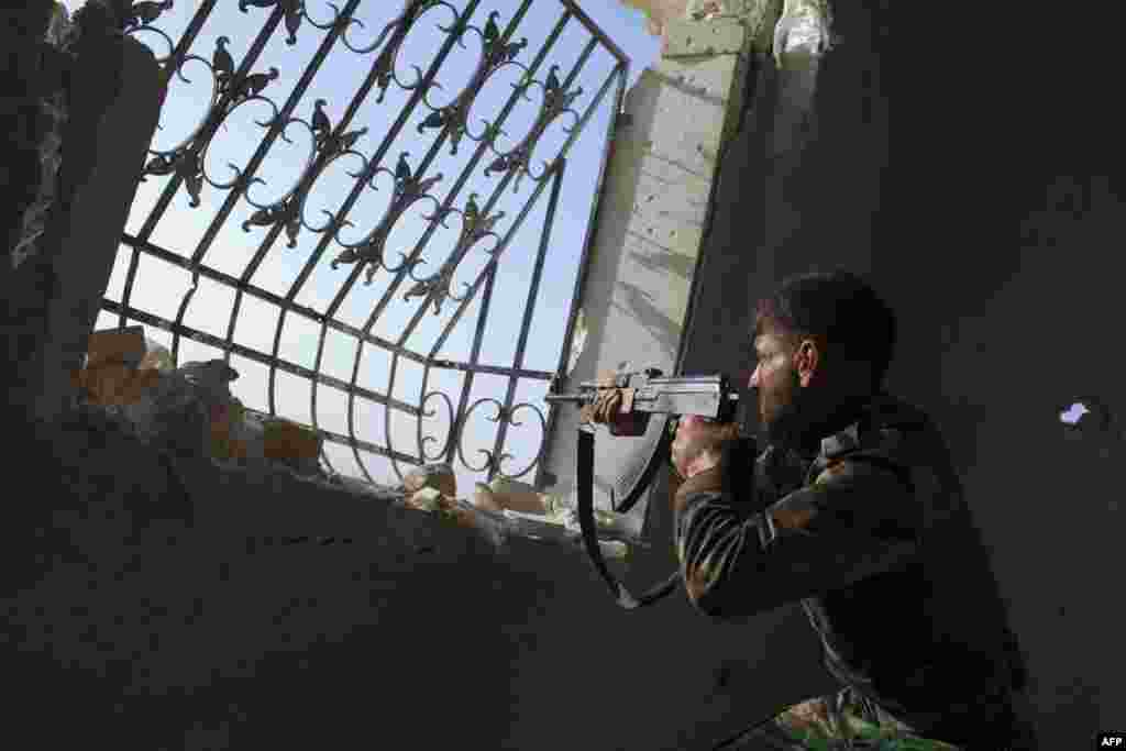A rebel Syrian fighter aims his weapon atgovernment forces' positions situated at the Menagh military airport near the northern city of Aleppo. (AFP/Jim Lopez)
