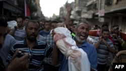 A Palestinian man shouts as he carries the body of 1-year-old baby Noha Mesleh, who died of wounds sustained after a UN school in Beit Hanun was hit by an Israeli tank shell, during her funeral in Beit Lahia in the Gaza Strip on July 25.