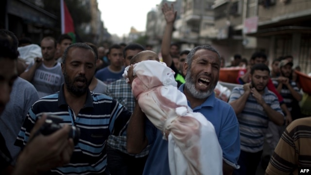 A Palestinian man cries as he carries the body of 1-year-old Noha Mesleh, who died of wounds sustained after a UN school in Beit Hanun was hit by an Israeli tank shell, during her funeral in Beit Lahia, northern Gaza Strip, on July 25.