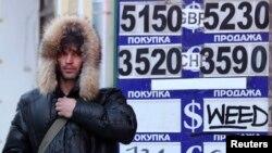 Мужчина идет рядом с пунктом обмена валют. Москва, 29 января 2014 года.