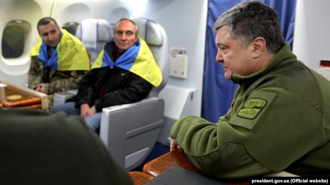 Президент України Петро Порошенко (праворуч) і звільнений з полону російських гібридних сил релігієзнавець Ігор Козловський (посередині), 27 грудня 2017 року