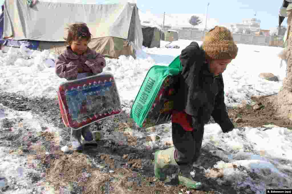 Displaced children carry winter supplies distributed by aid workers on the outskirts of Kabul on January 1.