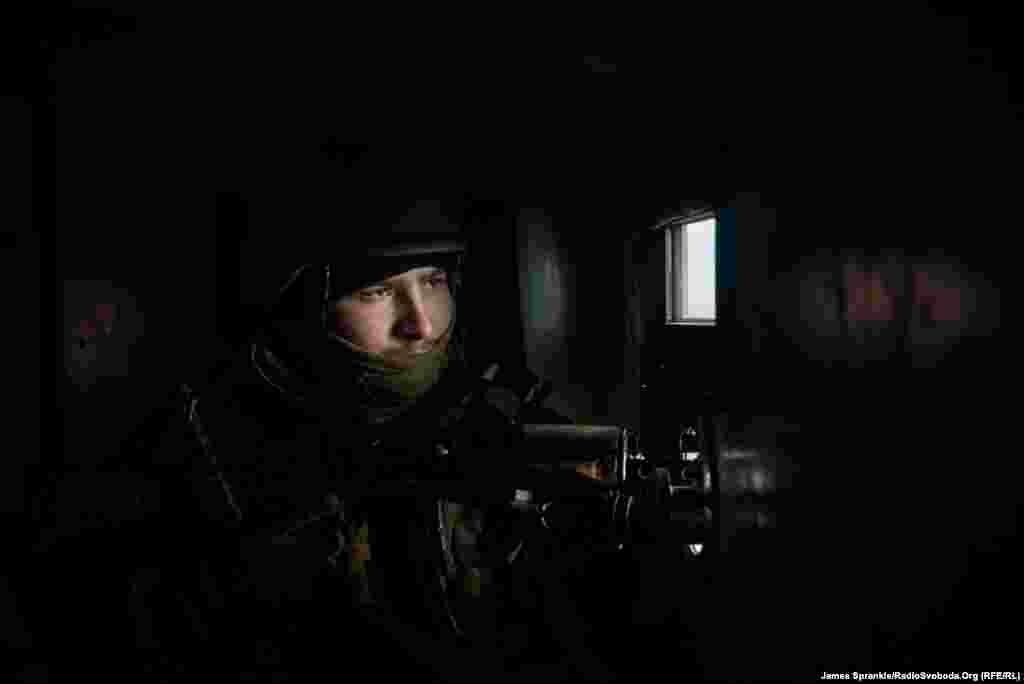 Молодий український солдат слідкує за ситуацією через спеціальне віконце броньованого автомобіля.