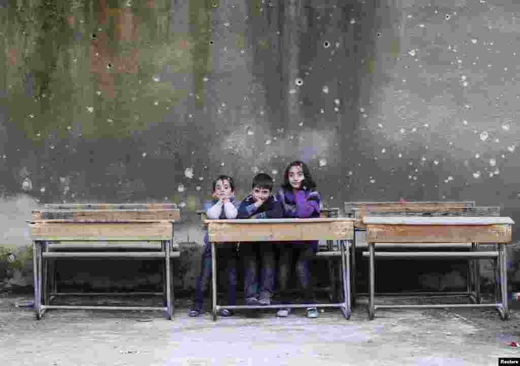 Children sit on school benches at the Al-Tawheed school in the besieged Syrian city of Aleppo. (Reuters/Muzaffar Salman)