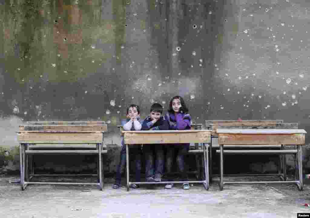 Children sit on school benches at the Al-Tawheed school in the besieged Syrian city of Aleppo. (Reuters/Muzaffar Salman)