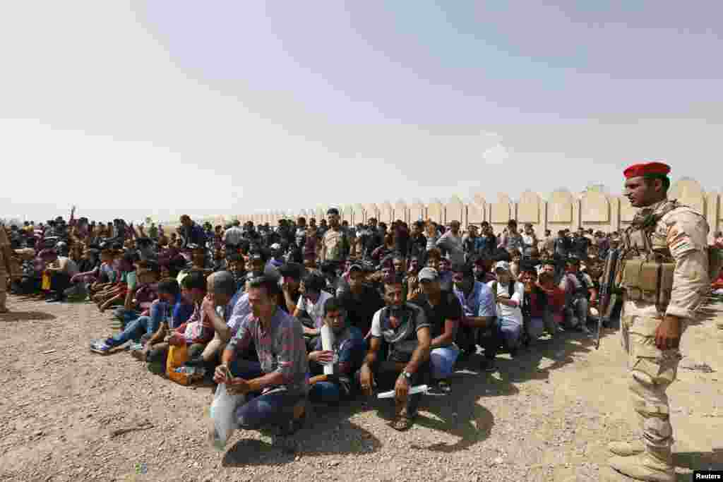 Volunteers waiting to join the Iraqi Army to fight against predominantly Sunni militants, who have taken over Mosul and other northern provinces, gather before boarding army trucks in Baghdad on June 13. (Reuters)