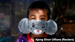 Панджі, 8 років, він носить маску у вигляді звірятка, щоб допомогти запобігти поширенню коронавірусу в Джакарті, Індонезія. 2 квітня 2020 року