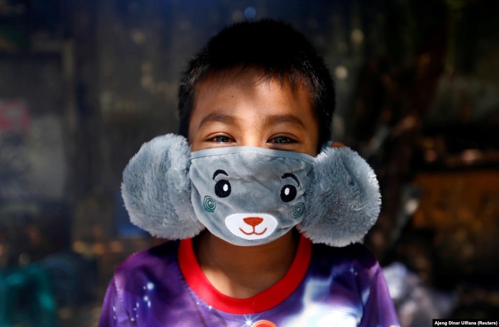 Восьмилетний Панджи носит маску в форме животного, чтобы предотвратить распространение коронавируса в Джакарте, Индонезия, 2 апреля.