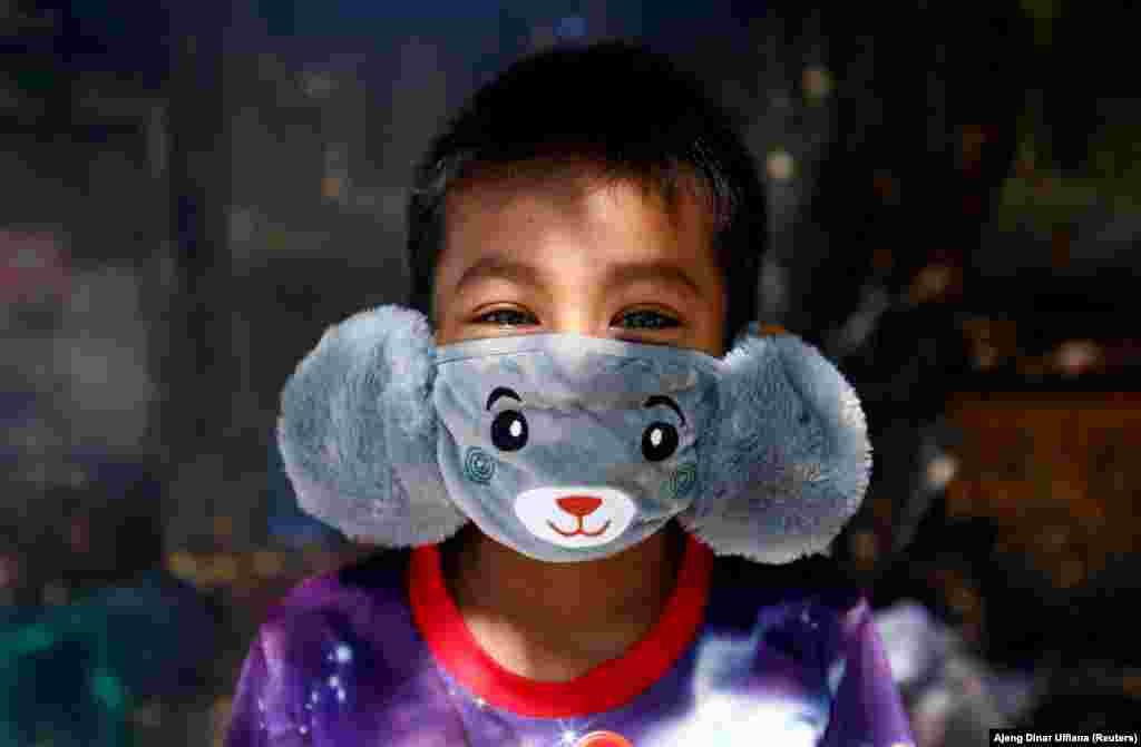 8-годишният Панджи носи маска с мишка срещу разпространението на коронавируса в Джакарта, Индонезия, 2 април.