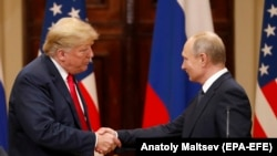 U.S. President Donald Trump (left) and Russian President Vladimir Putin shake hands following their summit talks in Helsinki on July 16.