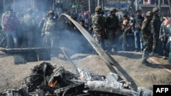 Indian soldiers and Kashmiri onlookers stand near the remains of an Indian Air Force aircraft after it crashed in Budgam district on February 27.