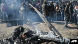 Indian soldiers and Kashmiri onlookers stand near the remains of an Indian Air Force aircraft after it crashed in the Budgam district, some 30 kilometers from Srinagar on February 27.