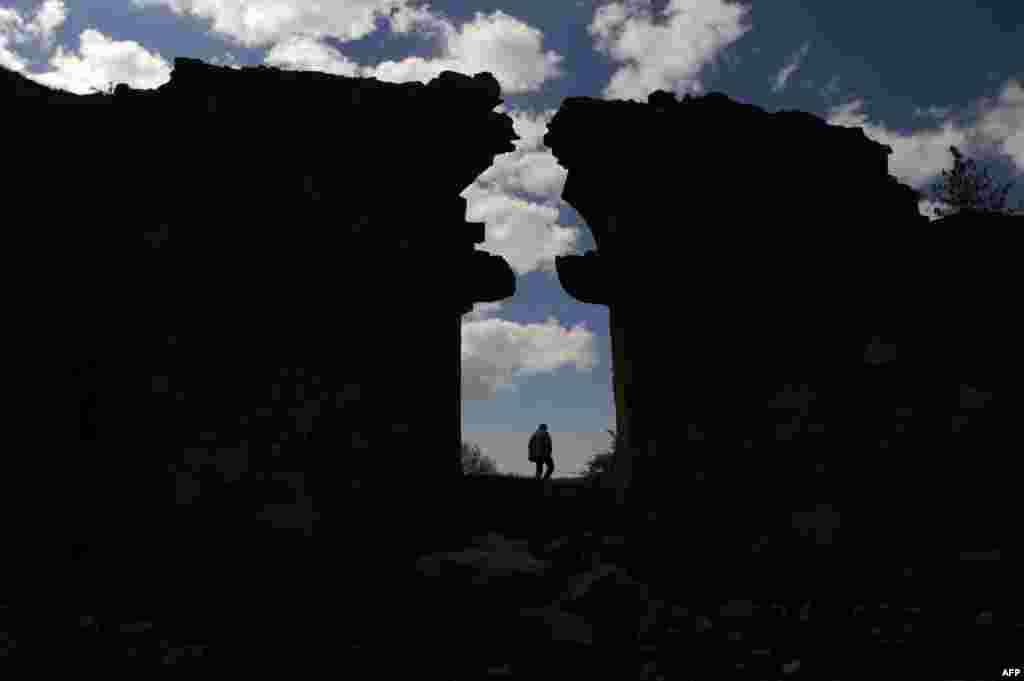 A resident of the eastern Turkish village of Hozat, also in Tunceli Province, walks in the ruins of an Armenian church.