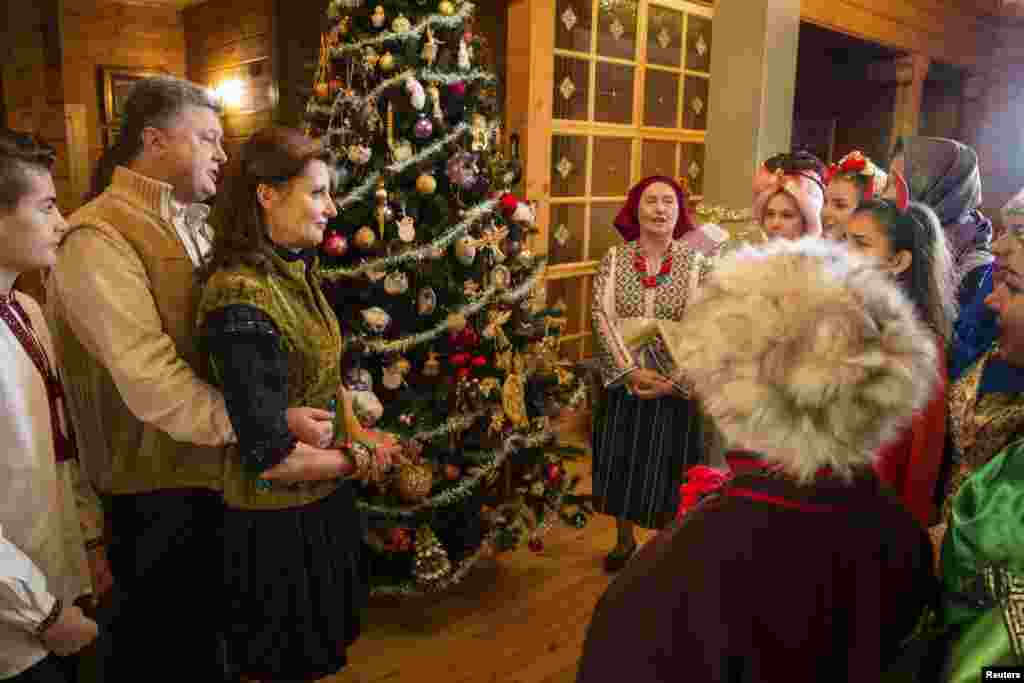 Ukraine -- Ukrainian President Petro Poroshenko (2nd L) and his wife Maryna (3rd L) meet with traditional Christmas carol singers at a state residence in the settlement of Huta in Ivano-Frankivsk region, western Ukraine, January 6, 2015